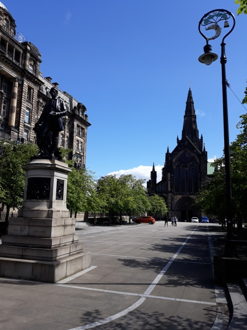 A view of the city with the characteristic lamp posts, which include a fish, tree, bell and bird, which are also included in Glasgow's city shield.